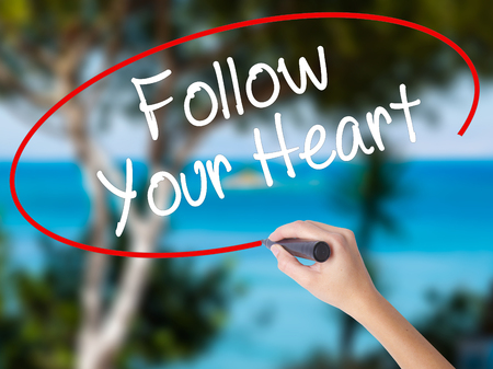 Woman Hand Writing Follow Your Heart with black marker on visual screen. Isolated on nature. Business concept. Stock Photo Stock Photo