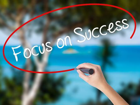 Woman Hand Writing Focus on Success with black marker on visual screen. Isolated on nature. Business concept. Stock Photo Stock Photo