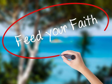 Woman Hand Writing Feed your Faith with black marker on visual screen. Isolated on nature. Business concept.