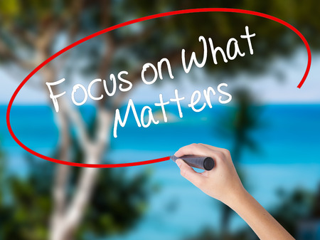 Woman Hand Writing Focus on What Matters with black marker on visual screen. Isolated on nature. Business concept. Stock Photo
