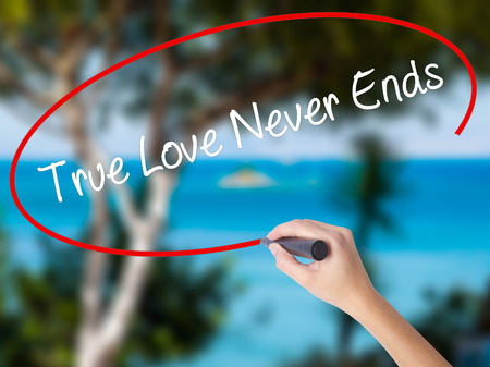 Woman Hand Writing True Love Never Ends with black marker on visual screen. Isolated on nature. Business concept. Stock Photo