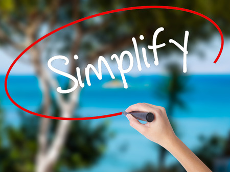 Woman Hand Writing Simplify with black marker on visual screen. Isolated on nature. Business concept. Stock Photo