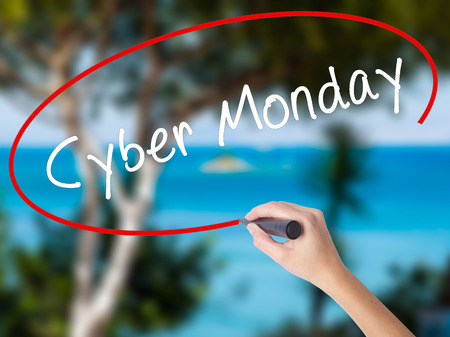 Woman Hand Writing Cyber Monday with black marker on visual screen. Isolated on nature. Business concept. Stock Photo