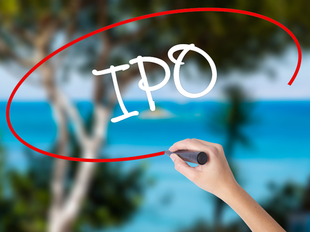 Woman Hand Writing IPO (Initial Public Offering)   with black marker on visual screen. Isolated on nature. Business concept. Stock Photo Stock Photo