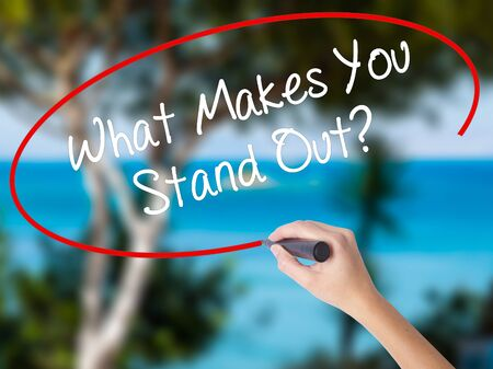 distinct: Woman Hand Writing What Makes You Stand Out? with black marker on visual screen. Isolated on nature. Business concept. Stock Photo