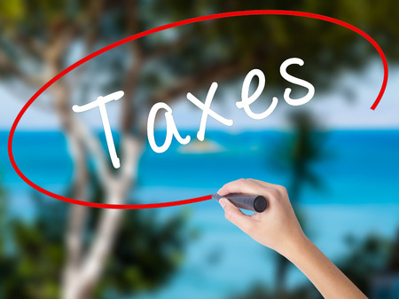 Woman Hand Writing Taxes with marker on transparent wipe board. Isolated on nature. Business, internet, technology concept. Stock Photo Standard-Bild