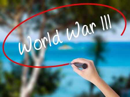 intolerancia: Mano de la mujer que escribe la guerra mundial lll con el marcador negro en la pantalla visual. Aislado en la naturaleza. Concepto de negocio. Foto de stock