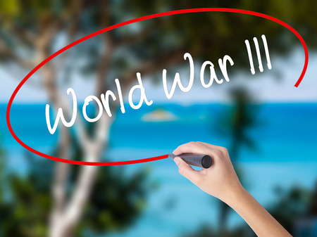 third world: Woman Hand Writing World War lll with black marker on visual screen. Isolated on nature. Business concept. Stock Photo