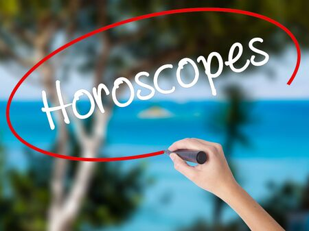 Woman Hand Writing Horoscopes  with black marker on visual screen. Isolated on nature. Business concept. Stock Photo