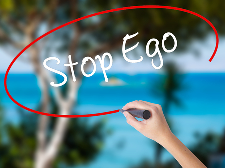 Woman Hand Writing  Stop Ego with black marker on visual screen. Isolated on nature. Business concept. Stock Photo