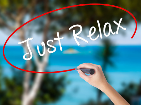 Woman Hand Writing Just Relax with black marker on visual screen. Isolated on nature. Business concept. Stock Photo