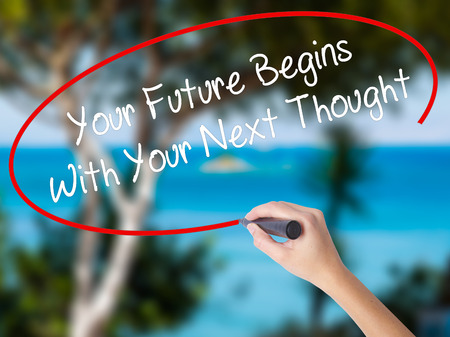 Woman Hand Writing Your Future Begins With Your Next Thought with black marker on visual screen. Isolated on nature. Business concept. Stock Photo Stock Photo