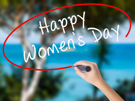 Woman Hand Writing Happy Womens Day with black marker on visual screen. Isolated on nature. Business concept. Stock Photo Stock Photo