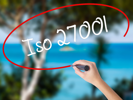 Woman Hand Writing Iso 27001  with black marker on visual screen. Isolated on nature. Business concept. Stock Photo