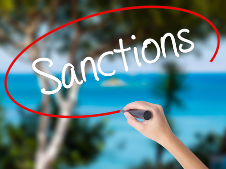 sanctioned: Woman Hand Writing Sanctions with black marker on visual screen. Isolated on nature. Business concept. Stock  Photo Stock Photo