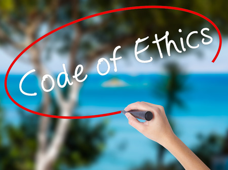 valores morales: Woman Hand Writing Code of Ethics with black marker on visual screen. Isolated on nature. Business concept. Stock Photo
