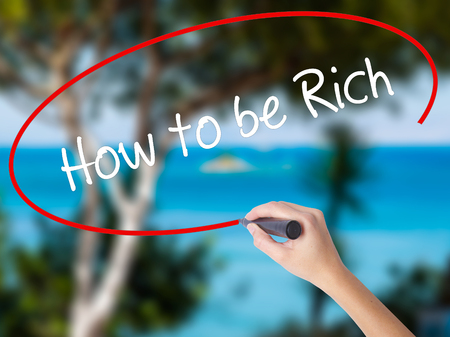 Woman Hand Writing How to be Rich  with black marker on visual screen. Isolated on nature. Business concept. Stock Photo