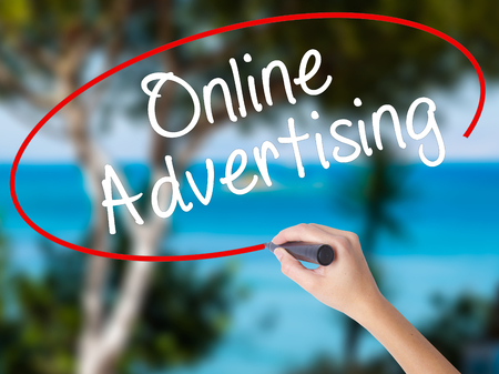 Woman Hand Writing Online Advertising with black marker on visual screen. Isolated on nature. Business concept. Stock Photo