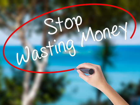 Woman Hand Writing Stop Wasting Money with black marker on visual screen. Isolated on nature. Business concept. Stock Photo