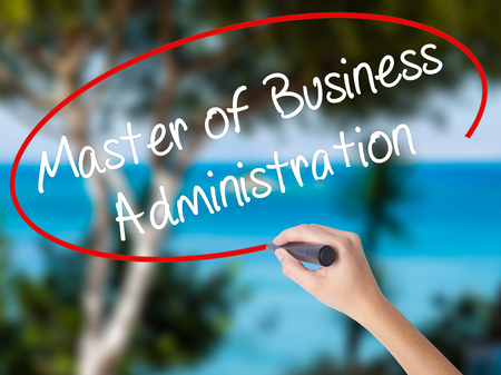Woman Hand Writing Master of Business Administration with black marker on visual screen. Isolated on nature. Business concept. Stock Photo