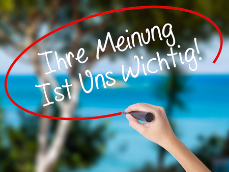 wichtig: Woman Hand Writing Ihre Meinung Ist Uns Wichtig! (Your Opinion is Important to Us in German) with marker on visual screen. Isolated on nature. Business concept. Stock Photo