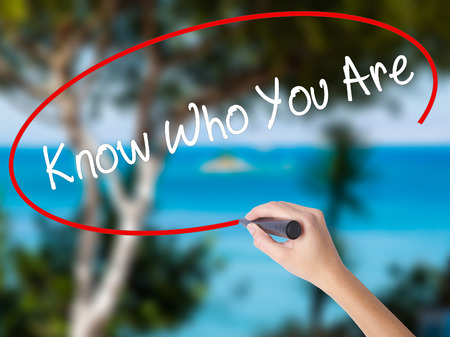 Woman Hand Writing Know Who You Are with black marker on visual screen. Isolated on nature. Business concept. Standard-Bild