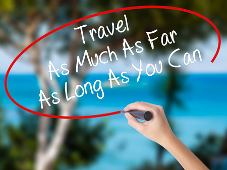 Woman Hand Writing Travel As Much As Far As Long As You Can  with black marker on visual screen. Isolated on nature. Business concept. Stock Photo