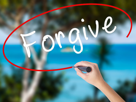 Woman Hand Writing Forgive with black marker on visual screen. Isolated on nature. Business concept. Stock Photo Stock Photo