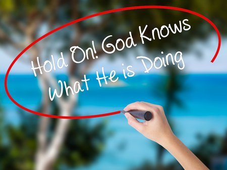 confessing: Woman Hand Writing Hold On! God Knows What He is Doing with black marker on visual screen. Isolated on nature. Business concept.