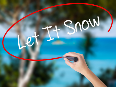 Woman Hand Writing Let It Snow with black marker on visual screen. Isolated on nature. Business concept. Stock Photo
