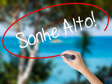Woman Hand Writing Sonhe Alto! (Dream Big in Portuguese) with black marker on visual screen. Isolated on nature. Business concept. Stock Photo Imagens