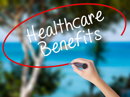 Woman Hand Writing Healthcare Benefits with black marker on visual screen. Isolated on nature. Business concept. Stock Photo