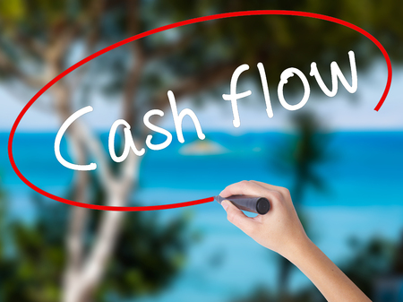 financial reward: Woman Hand Writing Cash flow with black marker on visual screen. Isolated on nature. Business concept. Stock Photo