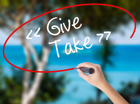 Woman Hand Writing Give - Take with black marker on visual screen. Isolated on nature. Business concept. Stock Photo