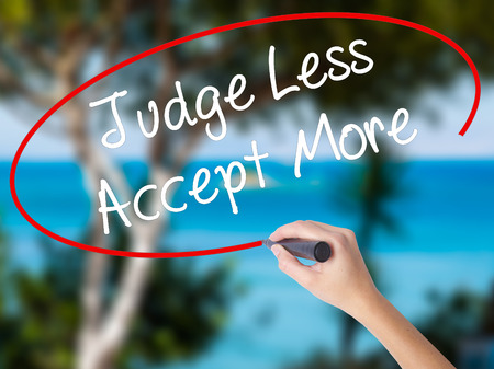 Woman Hand Writing Judge Less Accept More with black marker on visual screen. Isolated on nature. Business concept. Stock Photo