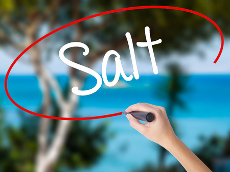Woman Hand Writing Salt with black marker on visual screen. Isolated on nature. Business concept. Stock Photo Stock Photo
