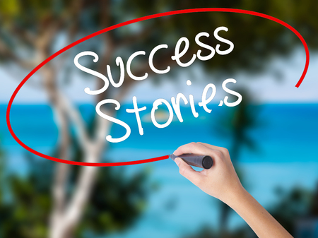 abilities: Woman Hand Writing Success Stories with black marker on visual screen. Isolated on nature. Business concept. Stock Photo