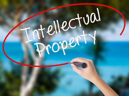 lawer: Woman Hand Writing Intellectual Property with black marker on visual screen. Isolated on nature. Business concept. Stock Photo