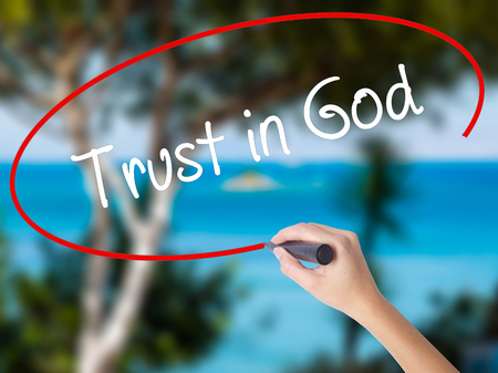 Woman Hand Writing Trust in God with black marker on visual screen. Isolated on nature. Business concept. Stock Photo
