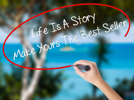 narrator: Woman Hand Writing Life Is A Story Make Yours The Best Seller with black marker on visual screen. Isolated on nature. Business concept. Stock Photo
