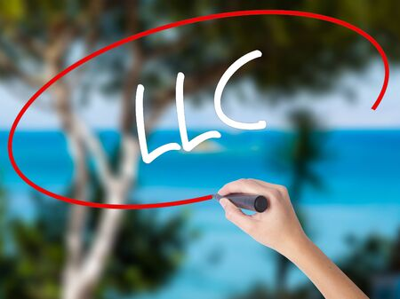 Woman Hand Writing  LLC (Limited Liability Company)  with black marker on visual screen. Isolated on nature. Business concept. Stock Photo Stock Photo
