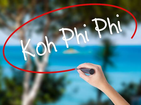 Woman Hand Writing Koh Phi Phi with black marker on visual screen. Isolated on nature. Business concept. Stock Photo Stock Photo