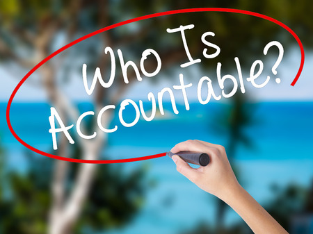 Woman Hand Writing Who Is Accountable? with black marker on visual screen. Isolated on nature. Business concept. Stock Photo Stock Photo
