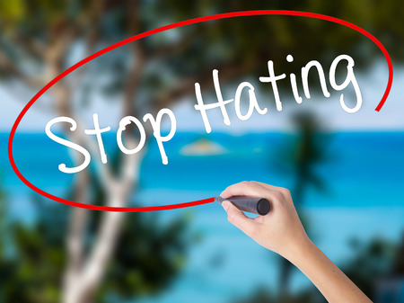 Woman Hand Writing Stop Hating  with black marker on visual screen. Isolated on nature. Business concept. Stock Photo