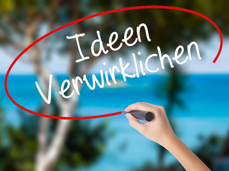 revelation: Woman Hand Writing Ideen Verwirklichen ( Realize Ideas in German) with black marker on visual screen. Isolated on nature. Business concept. Stock Photo
