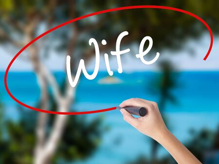 Woman Hand Writing Wife with black marker on visual screen. Isolated on nature. Business concept. Stock Photo Stock Photo