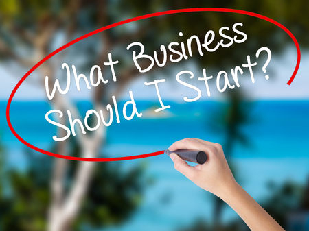 Woman Hand Writing What Business Should I Start? with black marker on visual screen. Isolated on nature. Business concept. Stock Photo