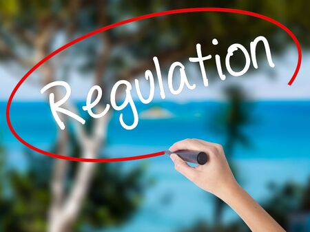 Woman Hand Writing Regulation  with black marker on visual screen. Isolated on nature. Business concept. Stock Photo