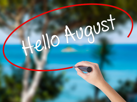 Woman Hand Writing Hello August with black marker on visual screen. Isolated on nature. Business concept. Stock Photo Stock Photo