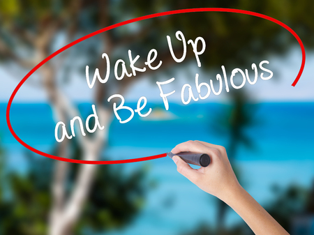 Woman Hand Writing Wake Up and Be Fabulous with black marker on visual screen. Isolated on nature. Business concept. Stock Photo Stock Photo